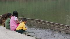 Kids feeding fish at lake,Rewalsar,Himachal Pradesh,India Stock Footage