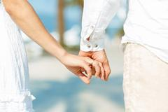 Concept shoot of love of man and woman: two hands over waterfront - stock photo