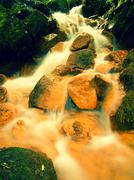Cascades in rapid stream of mineral water. Red ferric sediments on big boulde - stock photo