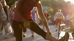 Athletic woman in pink tank top stretches in Central Park at sunset summer NYC Stock Footage