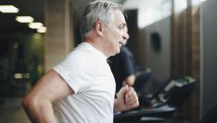 Senior man exercising on a treadmill in the gym. Right profile face footage Stock Footage