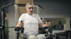Senior man lifting weights of his body in the gym - stock footage