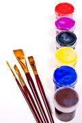 Bottles with gouache paints and brushes for artistic paintings. Stock Photos