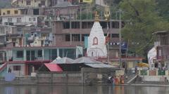 People feeding fish at lake with hindu temple,Rewalsar,Himachal Pradesh,India Stock Footage