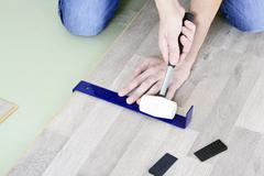 Man with Tools to Laying Laminate - stock photo