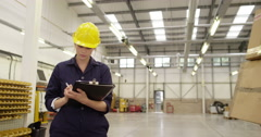 Warehouse manager works on a digital tablet while a worker shifts stock. Stock Footage