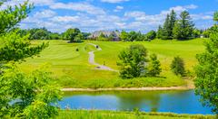 Golf place with pond and custom built luxury big house on background. - stock photo