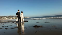 Asian Wedding Couple Walking Along the Beach at Sunset Stock Footage