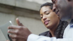 Stock Video Footage of 4k Attractive African American couple using digital tablet in the city