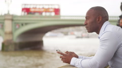 4K Man on his own in London, using mobile phone by the River Thames Stock Footage
