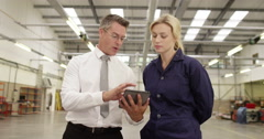 Manager and foreman in a factory using a digital tablet at a production line Stock Footage