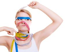 Obsessed sporty fit woman with measure tapes. Time for diet slimming. - stock photo