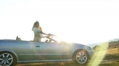 Young hipster having fun dancing in convertible cabriolet car. UHD 4K stock f Stock Footage