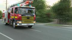 Fire truck races around road block Stock Footage