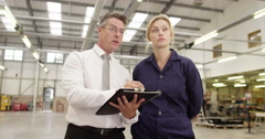Two factory managers standing with a clipboard at a production unit. Stock Footage