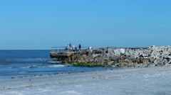 People gathering on rock jetty at the beach Stock Footage