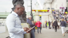 4k portrait of african american man using digital tablet on busy city street - stock footage