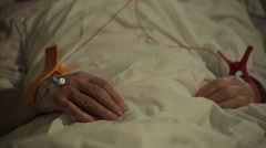Old patient attached to devices for monitoring vital functions. Hands close up. Stock Footage