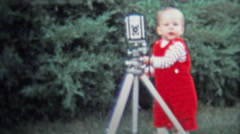 DALLAS, TX - 1971: Baby hilariously working the camera on a tripod. Stock Footage
