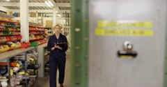 Portrait of an attractive female worker with a clipboard standing in a warehouse Stock Footage