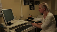 Neurologist sitting at the computer and monitors functions of brain to a patient Stock Footage