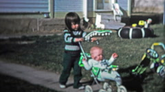 BOULDER, CO. USA - 1974: Little girl pushing baby brother around in a stoller. Stock Footage