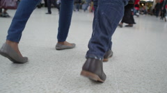 4K Low angle view of feet walking through a busy public area - stock footage