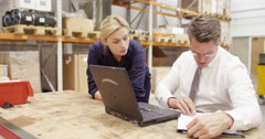 A warehouse manager checks and discusses stock levels on a laptop in a warehouse Stock Footage