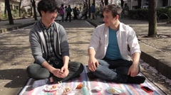 Caucasian and Japanese young men drinking sake during hanami party in Tokyo Stock Footage