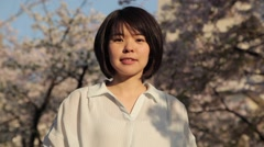 Portrait of a young Japanese woman in a city park in Tokyo Stock Footage
