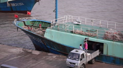 Fishermen moving sea products onto port from fishing ship Stock Footage
