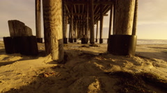 Wide angle under beach pier as waves roll in - stock footage