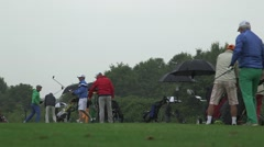 People warm up at golf course on a rainy day Stock Footage