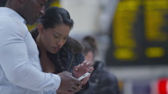 Couple looking at mobile phone in busy city train station Stock Footage