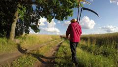 Farmer with scythe and rake on rural gravel road in summer. Timelapse 4K Stock Footage