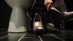 Girl changing her shoes and clothes in the toilet cabine - stock footage