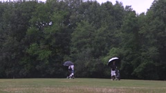 Golf player at golf course on a rainy day Stock Footage
