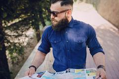 bearded man travels with map - stock photo