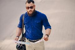 Bearded man travels with map Stock Photos