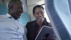 4k Happy attractive ethnic couple using computer tablet on train journey - stock footage