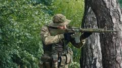 A man with a gun takes aim Stock Footage