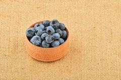 Handful of blueberries in wooden bowl on canvas - stock photo