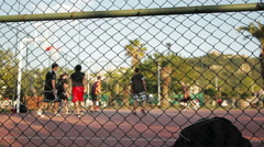 Young men play streetball (out of focus, focus on foreground). Stock Footage