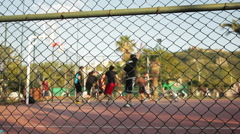 Young men play streetball (out of focus, focus on foreground). - stock footage