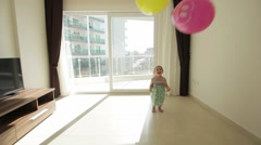 Cheerful little girl having fun with colorful balloons at home Stock Footage