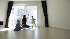 Young mother and her two little daughters wash the window in apartment. Stock Footage