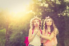 Best girlfriends are hiding lips behind lollipops. Sunset. - stock photo