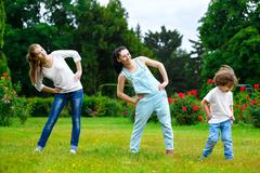 Portrait of happy family doing physical exercise or fitness in park - stock photo