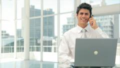 Businessman answering smart phone while using laptop at desk Stock Footage