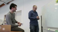 Two Man Draw Diagrams On The White Board And Discuss Stock Footage